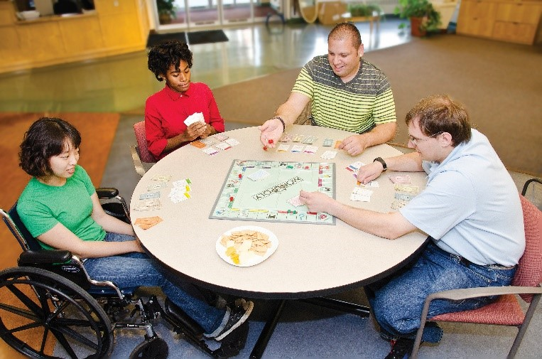 Group of adults playing a board game at a round table